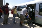 Patrons get on an express bus set up by the city to take people to a heat relief station inside the Phoenix Convention Center as temperatures climb to 112-degrees Friday, May 29, 2020, in Phoenix. (AP Photo/Ross D. Franklin)