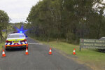 In this image made from a video, a police car blocks access to path near a beach in Coffs Harbour, Australia Sunday, Sept. 5, 2021. A surfer was fatally bitten by a shark off Australia's eastern coast Sunday as many locals went to beaches to celebrate Father's Day. (Australian Broadcasting Corporation via AP)