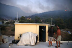 A local resident, right, speaks to a reporter on the wildfire in Peania, eastern Athens, Monday, Aug. 12, 2019. A big fire broke out in the Athens suburb of Peania east of the city, and authorities ordered the evacuation of nearby houses. (AP Photo/Thanassis Stavrakis)