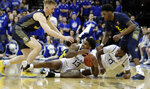 Seton Hall guard Myles Powell (13) tries to hold on to the ball as Marquette forward Sam Hauser, top, left, and forward Sacar Anim (2) challenge him during the first half of an NCAA college basketball game, Wednesday, March 6, 2019, in Newark, N.J. Seton Hall's Quincy McKnight (0) is seen on the play. (AP Photo/Julio Cortez)