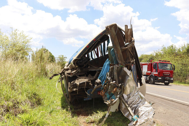 The wreckage of a bus that was carrying employees of a textile company remains on the shoulder of a road in the municipality of Taguai, about 350 kilometers (217 miles) from the city of Sao Paulo, Brazil, Wednesday, Nov. 25, 2020. The bus collided with a truck on a highway early Wednesday, killing 40 people, officials said. (AP Photo/Juliano Oliveira)