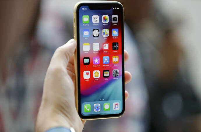 FILE - This Sept. 12, 2018, file photo shows an Apple iPhone XR on display at the Steve Jobs Theater after an event to announce new products, in Cupertino, Calif. A Chinese national in Oregon sent hundreds of supposedly broken iPhones to Apple over two years, and got replacements under warranty of almost 1,500 devices. (AP Photo/Marcio Jose Sanchez, File)