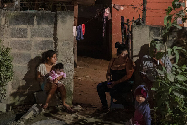 A family sits outside their home as forensic workers investigate a body at a crime scene in the Rivera Hernandez neighborhood of San Pedro Sula, Honduras on Nov. 30, 2019. MS-13. Mara 18. Los Vatos Locos _ The Crazy Guys. The gangs' shifting lines of control dodge and weave through Rivera Hernandez, a place where even the police are afraid. (AP Photo/Moises Castillo)