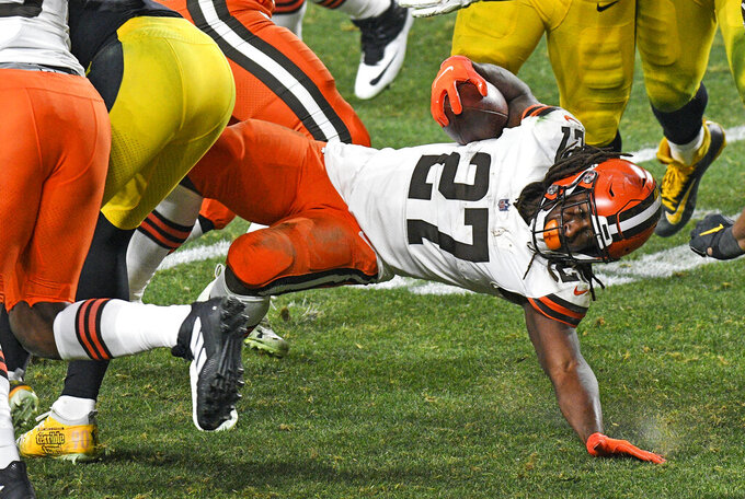 Cleveland Browns running back Kareem Hunt (27) is tackled during the second half of an NFL wild-card playoff football game against the Pittsburgh Steelers in Pittsburgh, late Sunday, Jan. 10, 2021. The Browns won 48-37.(AP Photo/Don Wright)