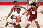 Houston guard DeJon Jarreau, front, passes the ball in front of Temple guard Jeremiah Williams, left, and forward Jake Forrester (10) during the first half of an NCAA college basketball game Tuesday, Dec. 22, 2020, in Houston. (AP Photo/Michael Wyke)