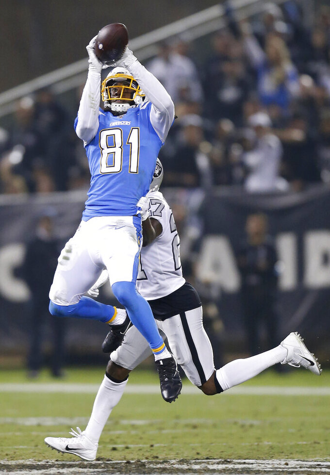 Los Angeles Chargers wide receiver Mike Williams (81) catches a pass in front of Oakland Raiders cornerback Trayvon Mullen during the second half of an NFL football game in Oakland, Calif., Thursday, Nov. 7, 2019. (AP Photo/D. Ross Cameron)