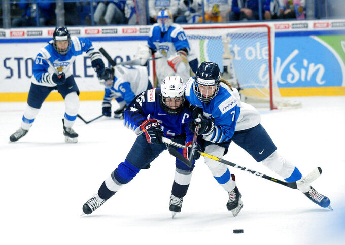FILE - Kendall Coyne Schofield, left, of the United States and Nelli Laitinen of Finland vie for the puck during the IIHF Women's Ice Hockey World Championships final match between the United States and Finland in Espoo, Finland, in this Sunday, April 14, 2019, file photo. The International Ice Hockey Federation is scrambling to reschedule the women's world hockey championships after health officials in Nova Scotia, Canada, on Wednesday, April 21, 2021, scrapped holding the tournament next month due to COVID-19 concerns. IIHF chief Rene Fasel told The Associated Press by phone he was blind-sided by the decision, which was made at essentially the last minute. (Mikko Stig/Lehtikuva via AP, File)
