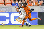 Austin FC midfielder Tomas Pochettino, left, is pushed by Houston Dynamo defender Teenage Hadebe (18) as they chase the ball during the first half of an MLS soccer match Saturday, Sept. 11, 2021, in Houston. (AP Photo/Michael Wyke)