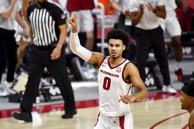 Arkansas forward Justin Smith (0) reacts after scoring against Auburn during the second half of an NCAA college basketball game Wednesday, Jan. 20, 2021, in Fayetteville, Ark. (AP Photo/Michael Woods)