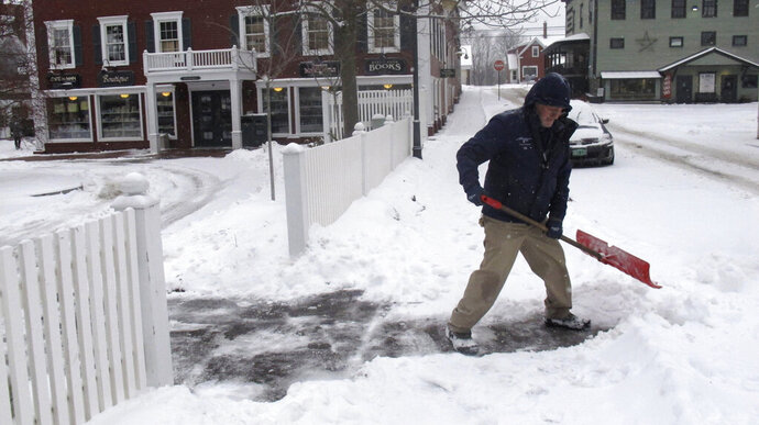 Bill Langley, of the Green Mountain Inn, in Stowe, Vt., shovels snow from a sidewalk on Tuesday, Nov. 12, 2019.  In the first significant snow of the season a wintry mix swept into northern New England, with hundreds of schools closed or delayed in Vermont due to snow, and slick conditions in New Hampshire and Maine. The National Weather Service says record cold could follow the snow. (AP Photo/Wilson Ring)