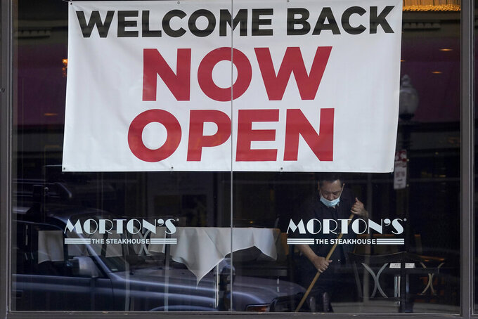 """FILE - In this March 4, 2021, file photo, a sign reading """"Welcome Back Now Open"""" is posted on the window of a Morton's Steakhouse restaurant as a man works inside during the coronavirus pandemic in San Francisco. California lost close to 70,000 jobs in January. But new numbers released Friday, March 12, 2021, by the state's Employment Development Department show the unemployment rate declined slightly to 9%. (AP Photo/Jeff Chiu, File)"""