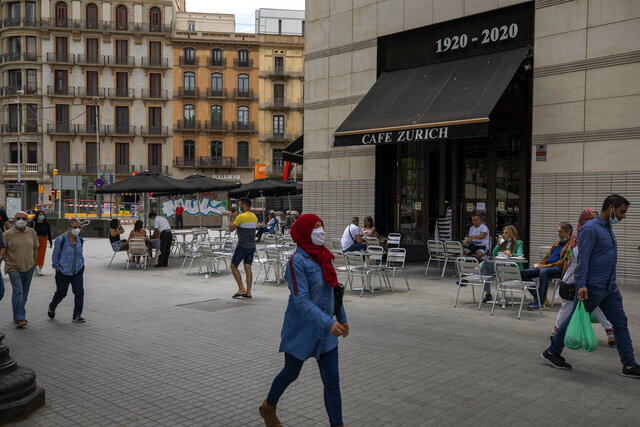 In this Monday, June 1, 2020 photo, people walk past a terrace bar with local customers in Barcelona downtown. Spain's strict lockdown that it is now scaling back managed to eventually control a COVID-19 outbreak that has claimed at least 27,000 lives. (AP Photo/Emilio Morenatti)
