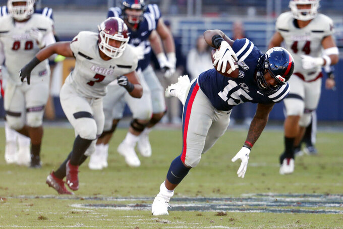 Mississippi tight end Octavious Cooley (15) stumbles forward after catching a pass past New Mexico State linebacker Javahn Fergurson (7) during the first half of an NCAA college football game in Oxford, Miss., Saturday, Nov. 9, 2019. (AP Photo/Rogelio V. Solis)