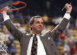 "FILE - In this March 27, 1993, file photo, Kansas coach Roy Williams raises his arms in victory after cutting a piece of the net after the NCAA Midwest Regional final in St. Louis. Williams' Jayhawks defeated Indiana 83-77 to advance to the Final Four in New Orleans. Williams paid tribute Wednesday, Sept. 9, 2020, to Gene Budig, a day after the former American League president and head of three major universities died at 81. ""He was the guy that gave Roy Williams a chance,"" Williams told The Associated Press. ""He made it OK for the athletic director to hire this no-name assistant coach from North Carolina as the head basketball coach at the University of Kansas."" (AP Photo/Seth Perlman, File)"
