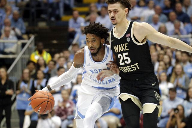 North Carolina's Leaky Black (1) drives on Wake Forest's Ismael Massoud (25) during the first half of an NCAA college basketball game in Chapel Hill, N.C., Tuesday, March 3, 2020. (AP Photo/Chris Seward)