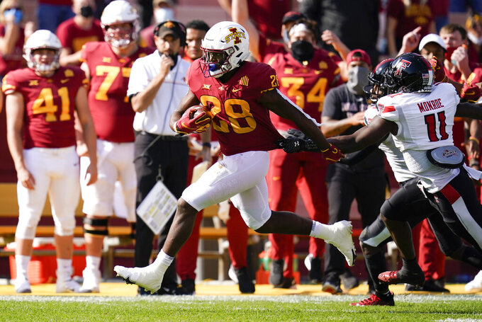 Iowa State running back Breece Hall (28) runs from Texas Tech defensive back Eric Monroe (11) during the first half of an NCAA college football game, Saturday, Oct. 10, 2020, in Ames, Iowa. (AP Photo/Charlie Neibergall)