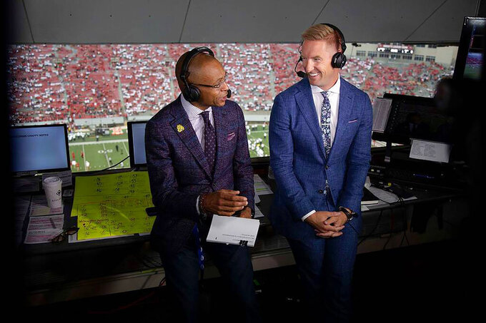 In a photo provided by Fox Sports, Gus Johnson, left, and Joel Klatt prepare for the Sept. 4, 2021, NCAA college football game between Penn State and Wisconsin in Madison, Wis. Johnson and Klatt will be on the call for Saturday's game when No. 4 Penn State visits third-ranked Iowa. The two began working together in 2015 when Klatt became Fox's top college football analyst after Charles Davis shifted over to NFL. (Fox Sports via AP)