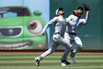Seattle Mariners' J.P. Crawford, left, and Mac Williamson chase a fly ball hit by Oakland Athletics' Khris Davis in the sixth inning of a baseball game Sunday, June 16, 2019, in Oakland, Calif. Crawford made the catch. (AP Photo/Ben Margot)