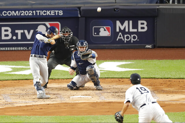 Tampa Bay Rays Brandon Lowe follows through on a three-run, home run off New York Yankees starting pitcher Masahiro Tanaka (19) during the third inning of a baseball game, Tuesday, Aug. 18, 2020, in New York. Yankees catcher Gary Sanchez is behind the plate as home plate umpire Chad Fairchild watches. (AP Photo/Kathy Willens)
