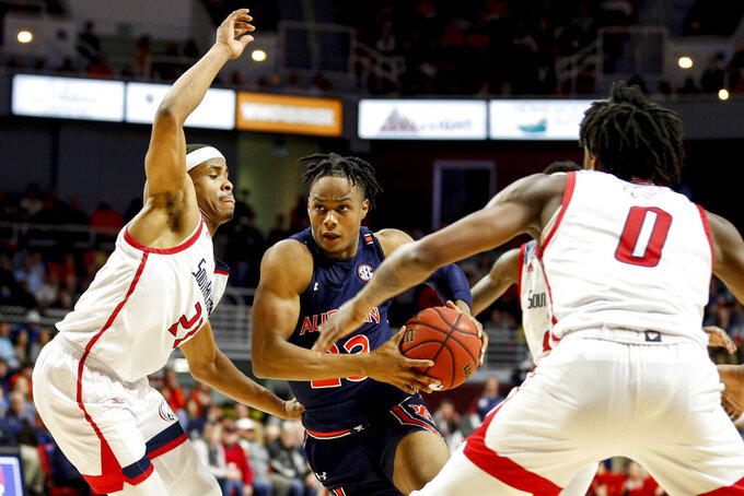 Auburn forward Isaac Okoro (23) drives to the basket between South Alabama guard Chad Lott (21) and forward KK Curry (0) during the first half of an NCAA college basketball game, Tuesday, Nov. 12, 2019, in Mobile, Ala. (AP Photo/Butch Dill)