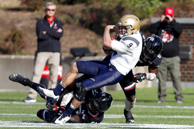 CORRETS TO TACKLED, NOT A SACK - Navy quarterback Zach Abey, center, is tackled by Cincinnati cornerback Arquon Bush, right, in the first half of an NCAA college football game, Saturday, Nov. 3, 2018, in Cincinnati. (AP Photo/John Minchillo)