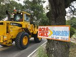 Construction equipment passes a homemade sign posted in the wake of Hurricane Dorian on North Carolina's Ocracoke Island on June 25, 2020. The secluded travel destination was ravaged by Dorian in September and then hit with coronavirus-related travel restrictions in the spring. Residents and business owners are hoping to recoup some of their losses as tourists return, albeit in smaller than usual numbers. But they're wary of a possibly busy hurricane season ahead. (AP Photo/Ben Finley).