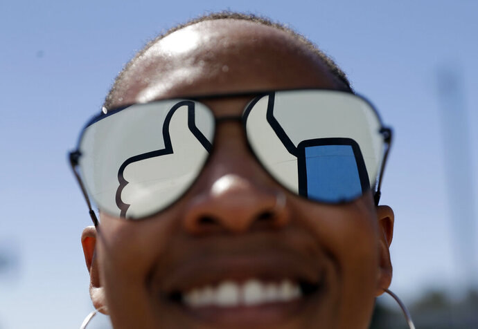FILE - In this March 28, 2018, file photo, a visitor poses for a photo with the Facebook logo reflected on her sunglasses at the company's headquarters in Menlo Park, Calif. Facebook reports earnings Wednesday, April 24, 2019. (AP Photo/Marcio Jose Sanchez, File)