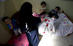 In this May 27, 2019, photo, Muna Awad, mother of 5-year-old Aisha a-Lulu, and her children sit on what used to be Aisha's bed at the family home in Burij refugee camp in central Gaza Strip. The death of the  Palestinian girl has drawn attention to Israel's vastly complex system for issuing travel permits to Gaza medical patients and their families. (AP Photo/Hatem Moussa)