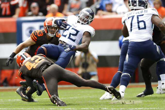 Cleveland Browns strong safety Morgan Burnett (42) trips up Tennessee Titans running back Derrick Henry (22) for a one-yard loss during the first half in an NFL football game, Sunday, Sept. 8, 2019, in Cleveland. (AP Photo/Ron Schwane)