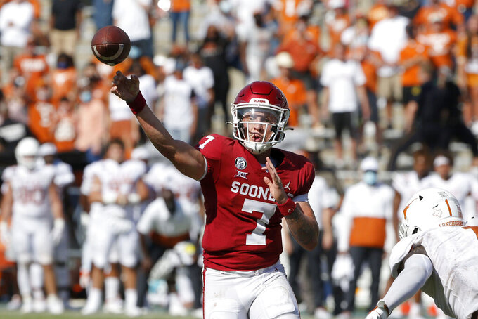 Oklahoma quarterback Spencer Rattler (7) throws a pass on a 2-point conversion against Texas during the fourth overtime of NCAA college football game in Dallas, Saturday, Oct. 10, 2020. Oklahoma defeated Texas 53-45 in four overtimes. (AP Photo/Michael Ainsworth)