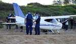 Police stand near a light plane that made an emergency landing on a beach in Sydney Wednesday, May 26, 2021. The recreational plane landed safely on a Sydney beach with three people aboard including a baby on Wednesday after its single engine failed, officials said. (AP Photo/Mark Baker)