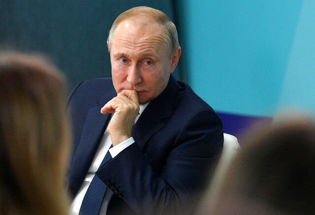 Russian President Vladimir Putin listens for a question as he visits the