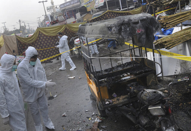 Pakistani investigators examine the site of bomb explosion in Rawalpindi, Pakistan, Friday, Dec. 4, 2020. A roadside bomb exploded near a busy bus terminal in the Pakistani garrison city of Rawalpindi, killing and and wounding some persons, police said. (AP Photo/A.H. Chaudary)
