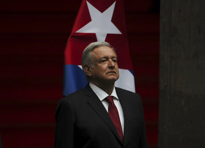 Mexico's President Andres Manuel Lopez Obrador listens the national anthem during a welcoming ceremony for his Cuban counterpart, Miguel Diaz-Canel at the National Palace in Mexico City, Mexico, Thursday, Oct. 17, 2019. (AP Photo/Fernando Llano)