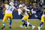 Los Angeles Chargers quarterback Easton Stick (2) scrambles as he looks for a receiver during the second half of the team's NFL football preseason game against the Seattle Seahawks on Saturday, Aug. 28, 2021, in Seattle. (AP Photo/Elaine Thompson)