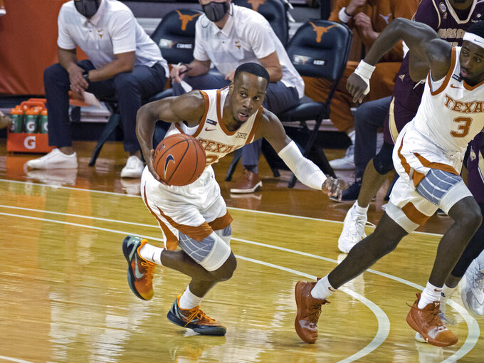 Texas guard Matt Coleman III breaks away with the ball during the first half of the team's NCAA college basketball game against Texas State, Wednesday, Dec. 9, 2020, in Austin, Texas. (AP Photo/Michael Thomas)