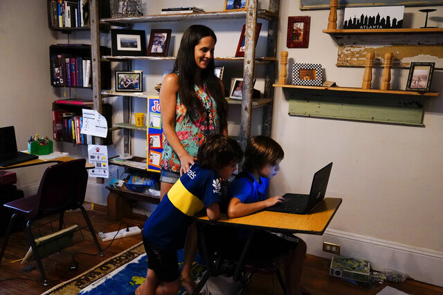 Anna Hamilton, 43, center, poses for a photograph with her sons, Henry, 6, left, and Adrian, 7, right, in their home on Monday, Aug. 24, 2020, in Decatur, Ga.  Hamilton is taking leave from her job at a small investment firm where she has worked for 12 years so she can guide her children through remote schooling. Looking back, she sees how childcare responsibilities, doctor visits, school pick-ups, lining up babysitters, often fell on her as the parent with the more flexible job. (AP Photo/Brynn Anderson)
