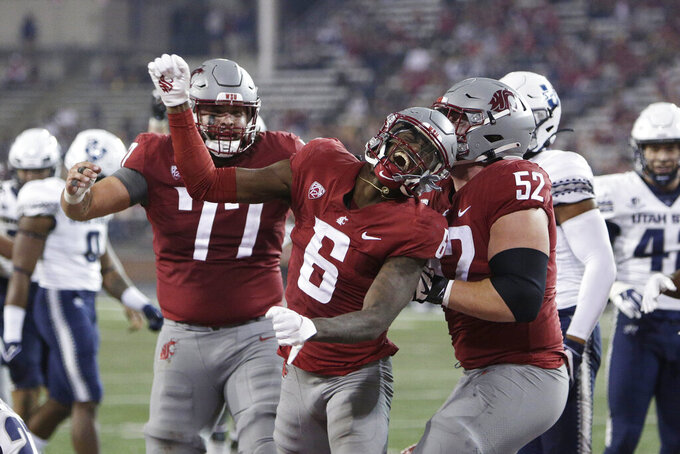 Washington State wide receiver Donovan Ollie (6) celebrates his touchdown with offensive lineman Konner Gomness (77) and offensive lineman Jarrett Kingston (52) during the second half of an NCAA college football game against Utah State, Saturday, Sept. 4, 2021, in Pullman, Wash. Utah State won 26-23. (AP Photo/Young Kwak)