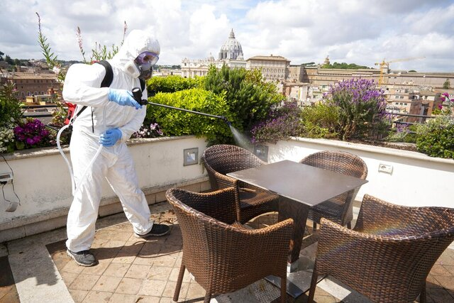 A worker disinfects the roof terrace of the Atlantic hotel, in Rome, Wednesday, April 29, 2020. After seven weeks in lockdown to contain one of the world's worst outbreaks of COVID-19, Italians are regaining some freedoms, starting on May 4, public parks and gardens will re-open and people will be able to visit relatives who live in the same region. (AP Photo/Andrew Medichini)