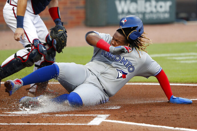 Toronto Blue Jays' Vladimir Guerrero Jr. scores on a sacrifice fly by Danny Jansen in the second inning of a baseball game against the Atlanta Braves Wednesday, Aug. 5, 2020, in Atlanta. (AP Photo/John Bazemore)