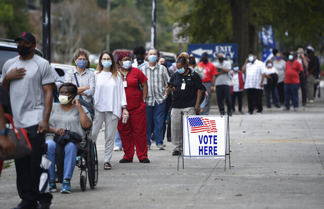 FILE - In this Oct. 12, 2020, file photo, voters wait in line to cast their ballot early at the Bell Auditorium in Augusta, Ga. Black people are going to the polls by the thousands and waiting in lines for hours to vote early in Georgia. (Michael Holahan/The Augusta Chronicle via AP, File)