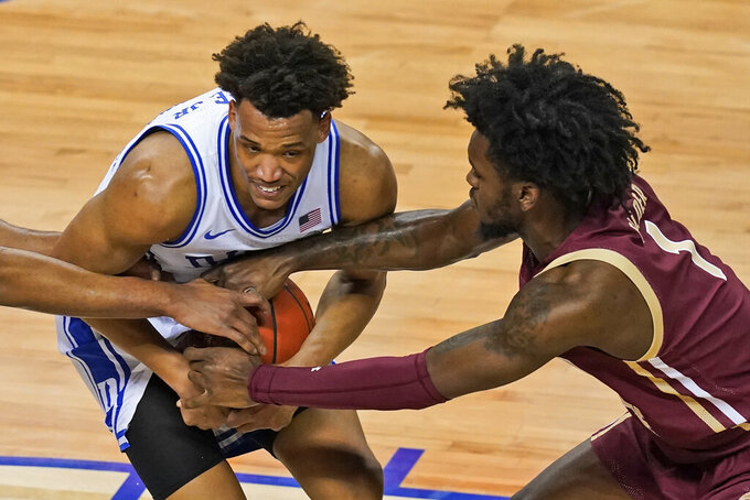 Boston forward CJ Felder (1) reaches it to grab the ball from Duke forward Jalen Johnson, left, during the first half of an NCAA college basketball game in the first round of the Atlantic Coast Conference tournament in Greensboro, N.C., Tuesday, March 9, 2021. (AP Photo/Gerry Broome)
