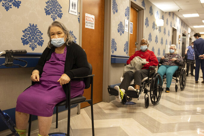 FILE - In this Friday, Jan. 15, 2021 file photo, nursing home residents wait on line to receive a COVID-19 vaccine at Harlem Center for Nursing and Rehabilitation, a nursing home facility in the Harlem neighborhood of New York.  After a deadly year in New York's nursing homes, state lawmakers have passed legislation that could potentially force facility owners to spend more on patient care.   (AP Photo/Yuki Iwamura, File)