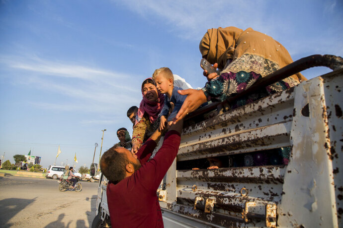 Syrians fleeing Turkish advance arrive to the town of Tal Tamr in north Syria, Monday, Oct. 14, 2019. Syrian government troops moved into towns and villages in northern Syria on Monday, setting up a potential clash with Turkish-led forces advancing in the area as long-standing alliances in the region begin to shift or crumble following the pullback of U.S. forces. (AP Photo/Baderkhan Ahmad)