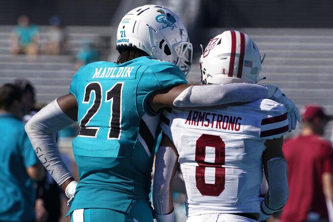 Coastal Carolina tight end Logan Mauldin (21) hugs Massachusetts defensive back Tristan Armstrong (8) after Coastal Carolina's win in an NCAA college football game on Saturday, Sept. 25, 2021, in Conway, S.C. (AP Photo/Chris Carlson)