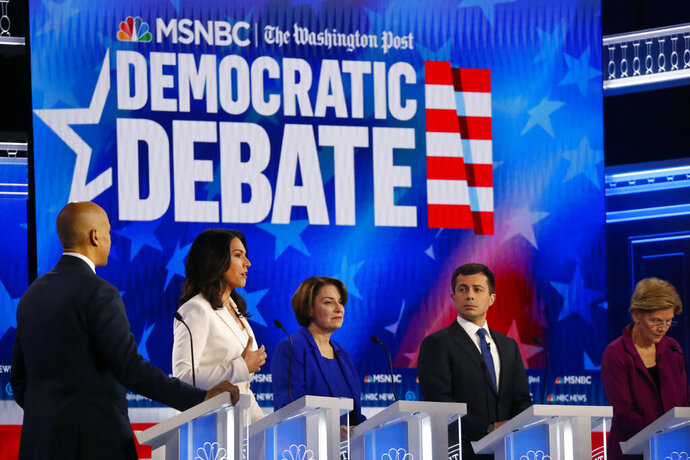 Democratic presidential candidate Rep. Tulsi Gabbard, D-Hawaii, second from left, speaks as other candidate including Sen. Cory Booker, D-N.J., left, Sen. Elizabeth Warren, D-Mass., South Bend, Ind., Mayor Pete Buttigieg and Sen. Amy Klobuchar, D-Minn., listen during a Democratic presidential primary debate, Wednesday, Nov. 20, 2019, in Atlanta. (AP Photo/John Bazemore)