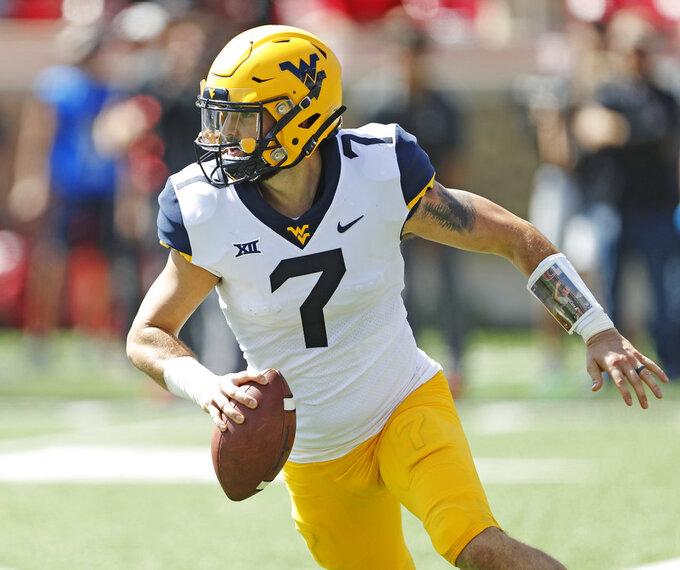 FILE - In this Saturday, Sept. 29, 2018, file photo, West Virginia's Will Grier (7) looks to pass during the second half of an NCAA college football game against Texas Tech in Lubbock, Texas. With Heisman Trophy-contending quarterback Will Grier, the Mountaineers are the Big 12's only remaining undefeated team.  (AP Photo/Brad Tollefson, File)