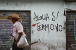 A farmer walks past graffiti that reads in Spanish