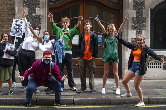 Students outside the Department for Education building in London, react to news of the policy U-turn on the system for awarding A-level and GCSE grades, Monday Aug. 7, 2020.   Exam-grading policy was set because no exams were possible because of the coronavirus.  The British government has scrapped an exam-grading policy that was set to deprive thousands of 18-year-olds, especially the more disadvantaged, of their university places. (Victoria Jones/PA via AP)
