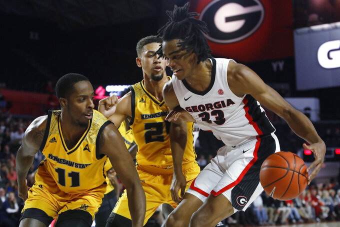Georgia forward Nicolas Claxton (33) tries to get by Kennesaw State forward Bryson Lockley (24) and guard Kyle Clarke (11) during an NCAA college basketball game in Athens, Ga., Tuesday, Nov. 27, 2018. (Jenn Finch/Athens Banner-Herald via AP)